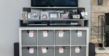 IKEA cube storage makeover with an added shelf on top and tv and picture frames on top