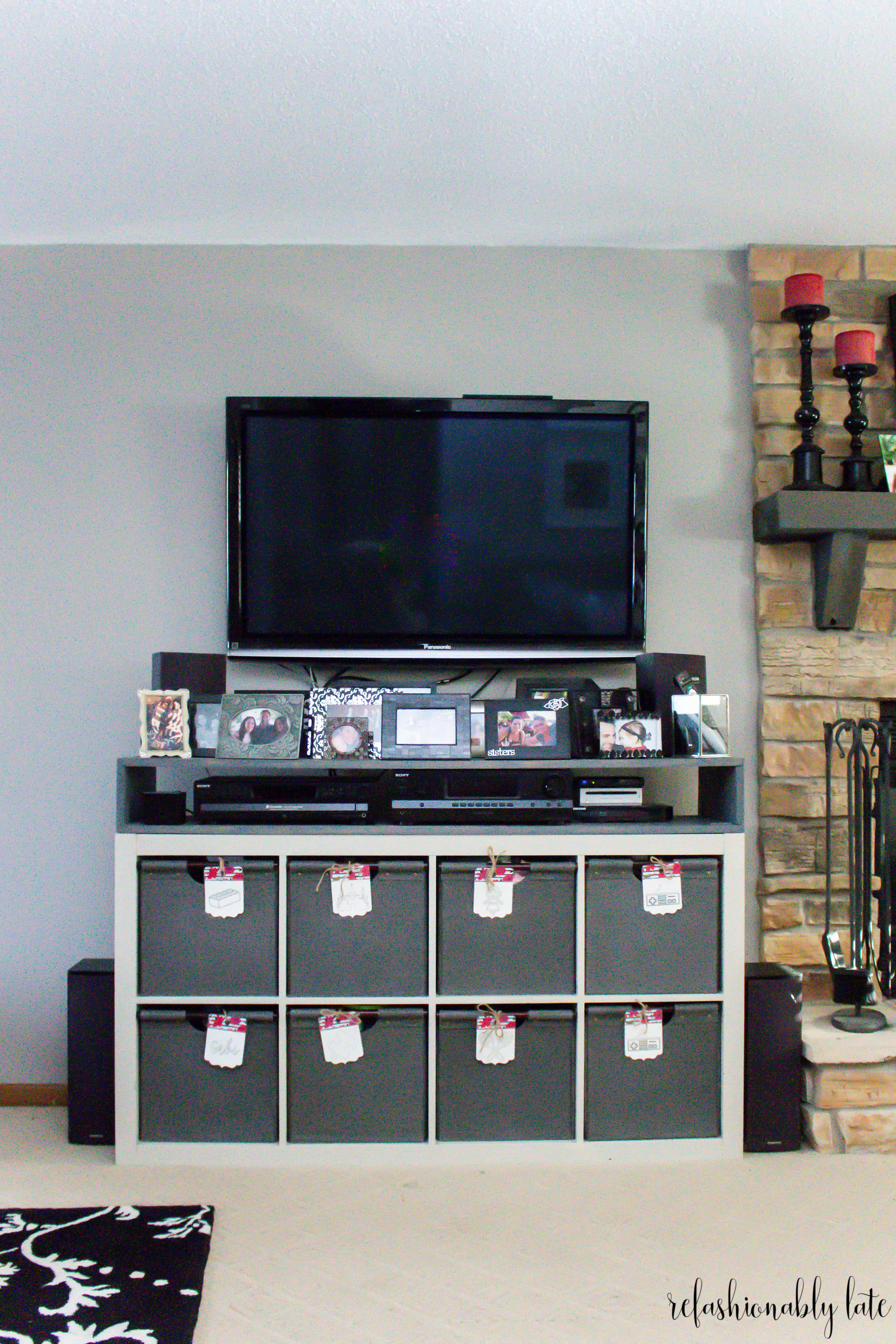 IKEA Kallax hack with a built on shelf at the top with stereo equipment inside and a TV mounted on the wall