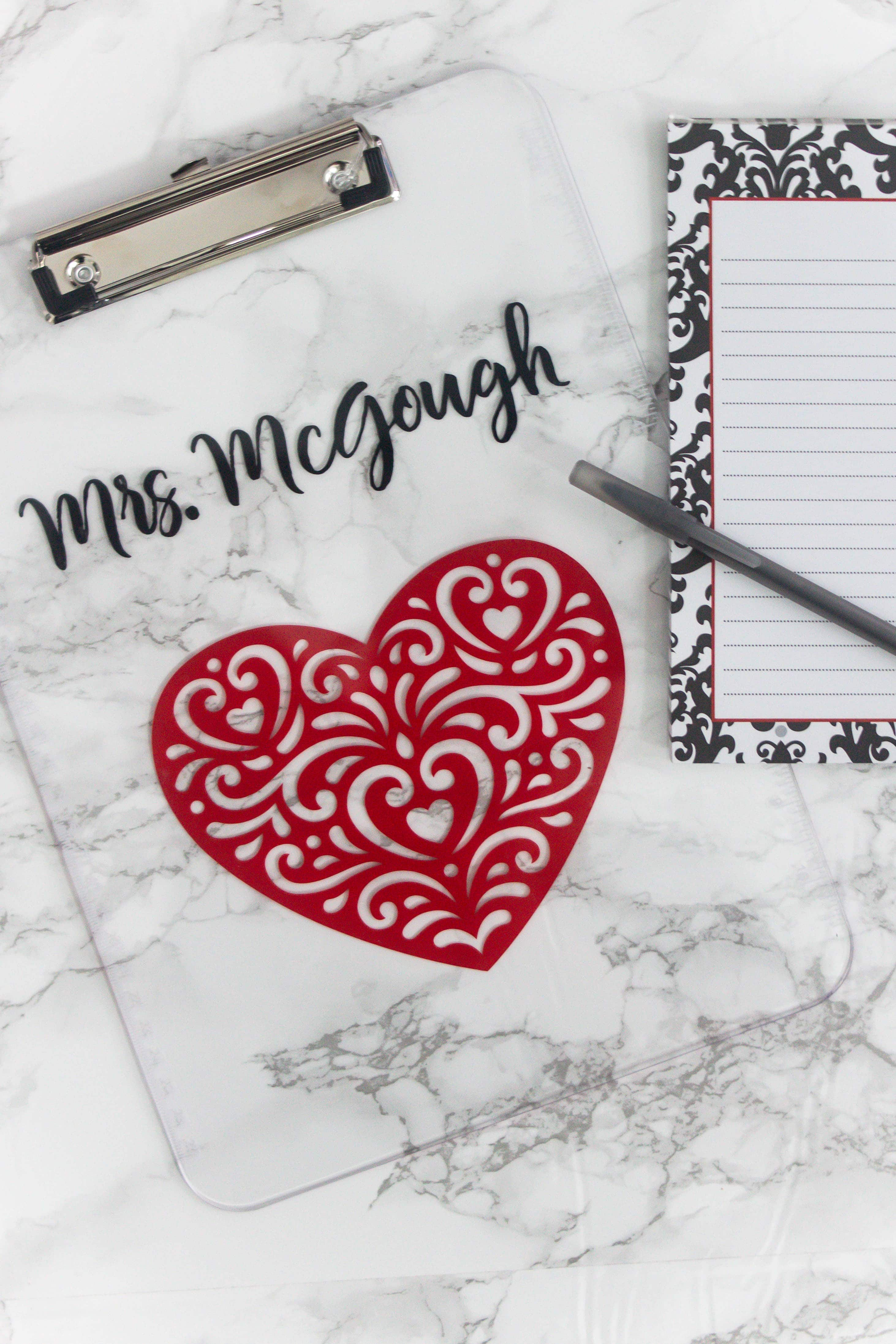 DIY personalized clipboard with marble background and and a heart and name at the top with a notepad and pen