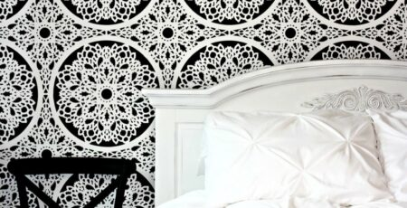 black and white feature wall with white bed and a black chair next to it