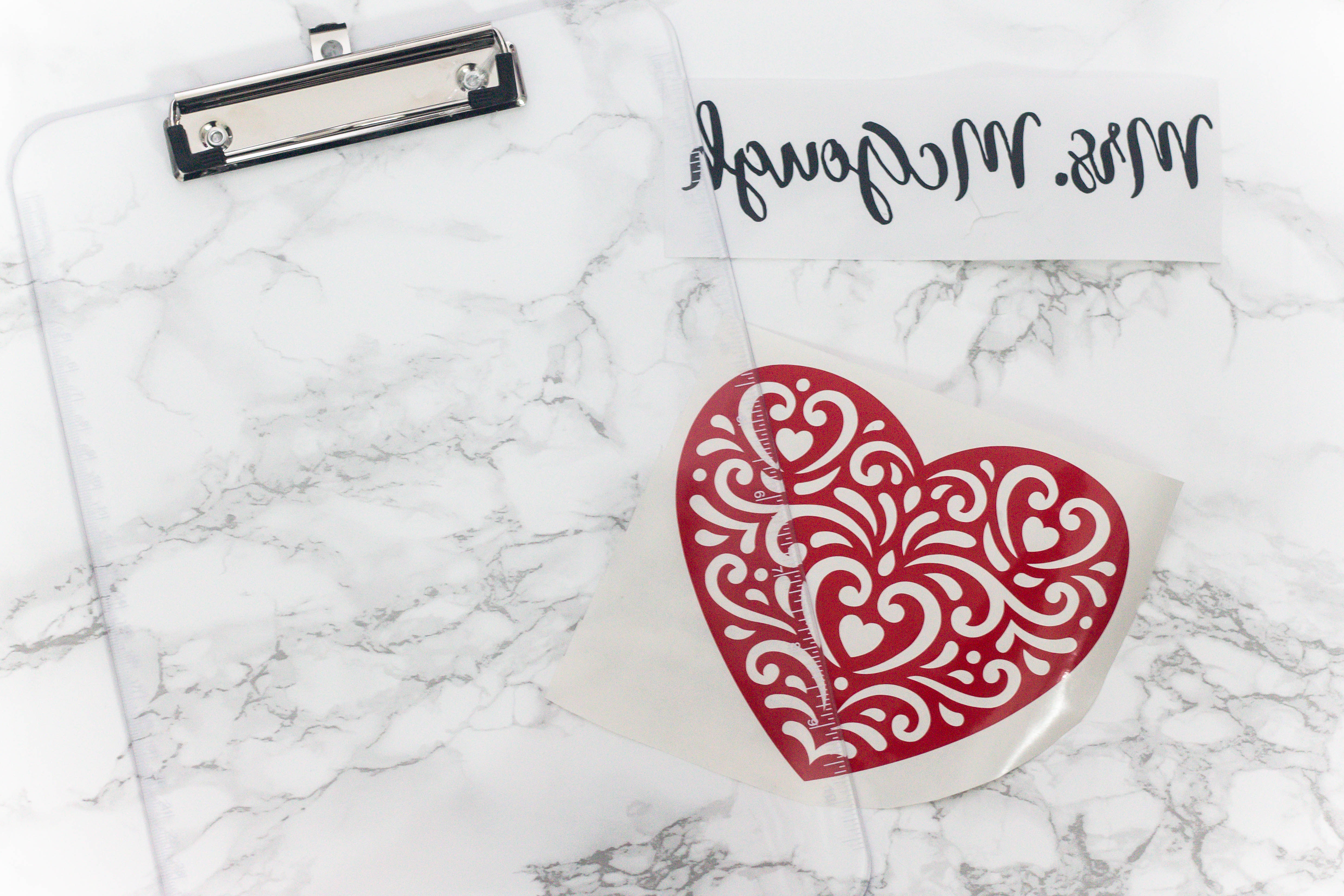 marble countertop with a clear clipboard and a heart image and a name mirrored