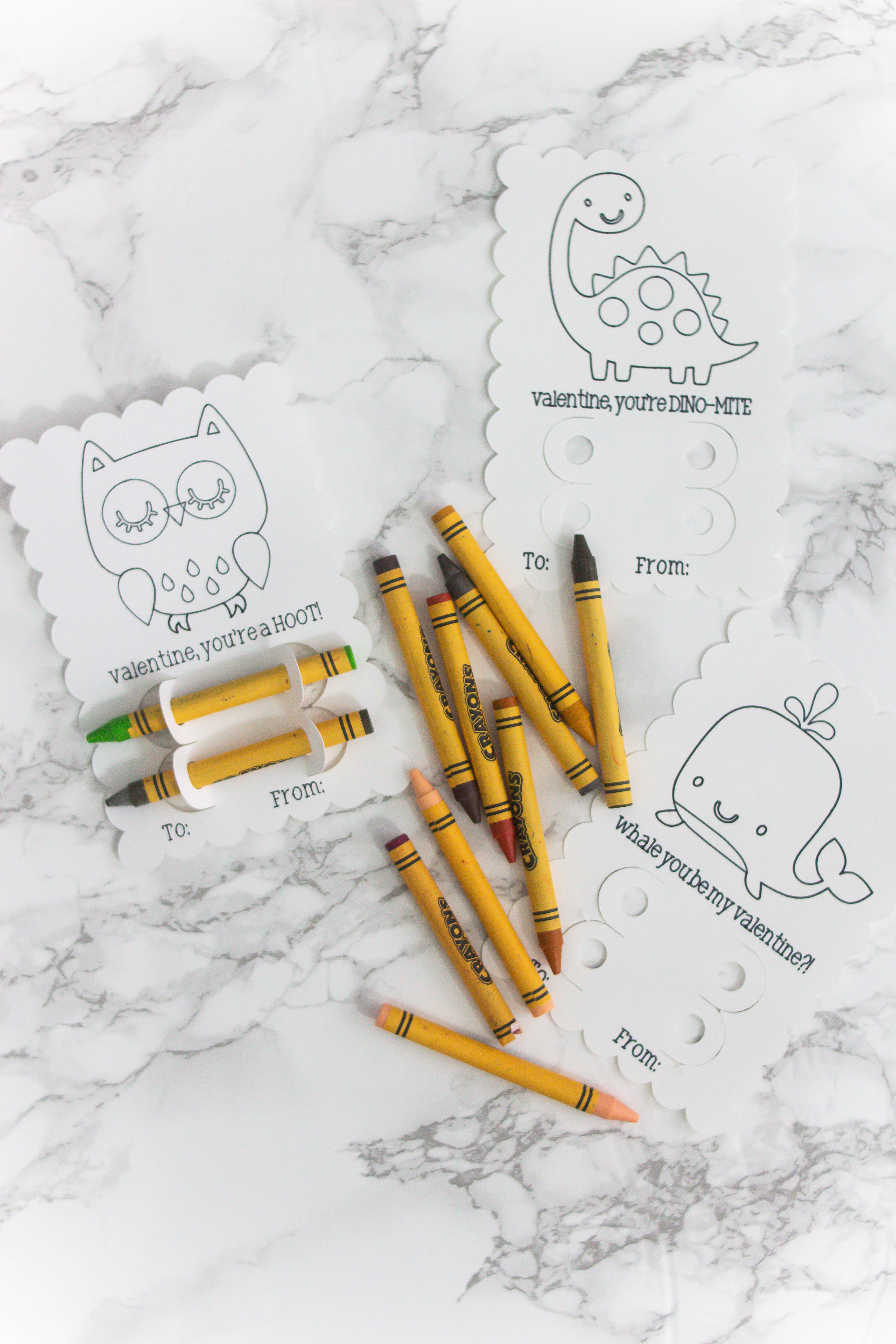 white valentines with owls dinosaurs and whales with crayons to color them in on a marble countertop