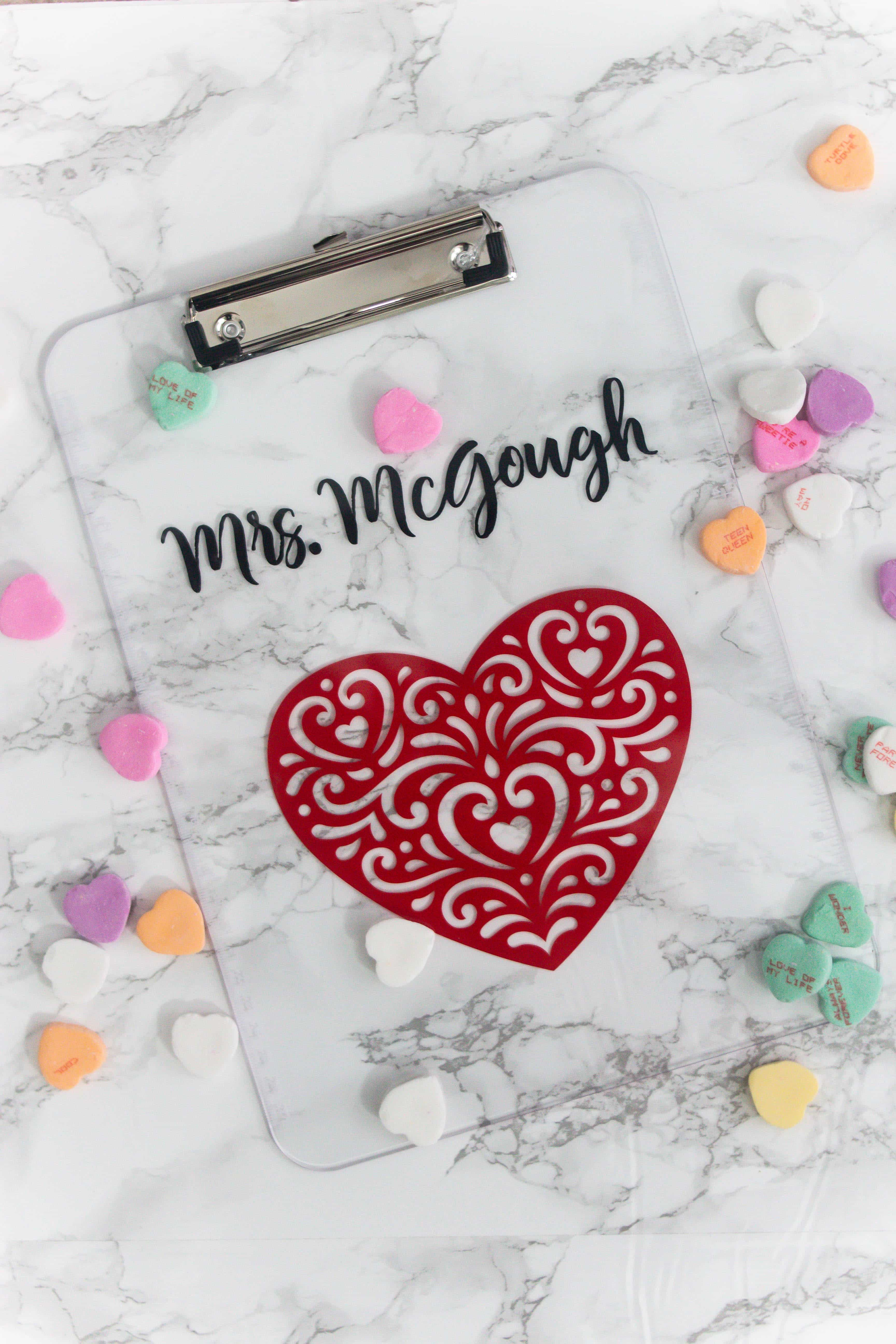 marble background with clear clipboard with heart image and name on the top with candy hearts all around it