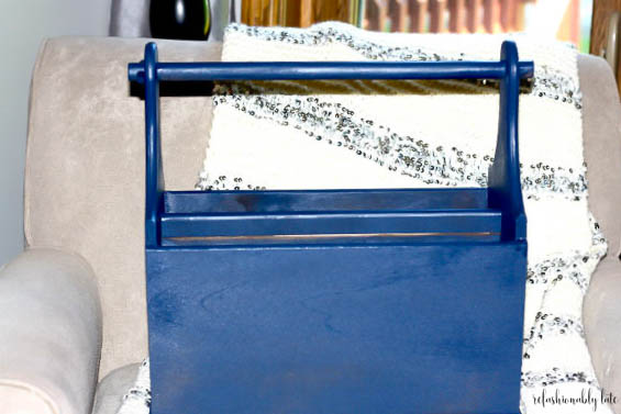 Blue painted magazine rack sitting on a tan chair