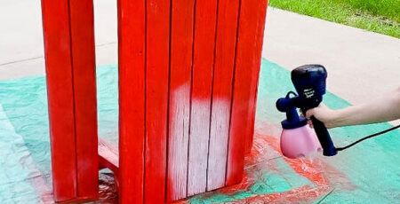 children's picnic table set on it's side being painted red with a HomeRight paint sprayer