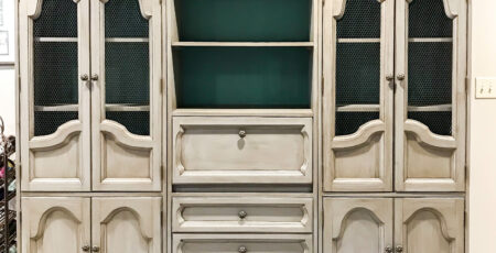 grey hutch with a blue back sitting in a family room