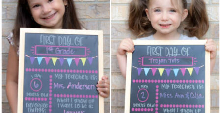 two girls holding first day of school chalkboards