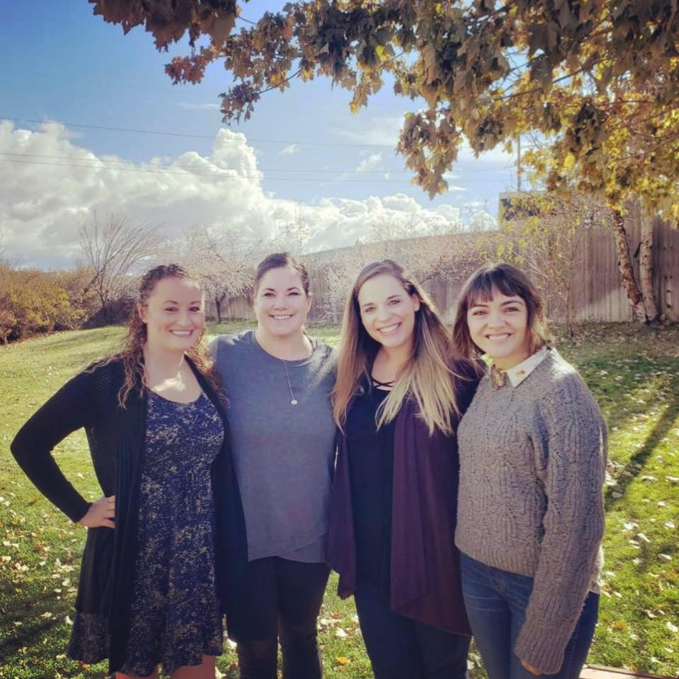 4 women posing together outside on a fall day