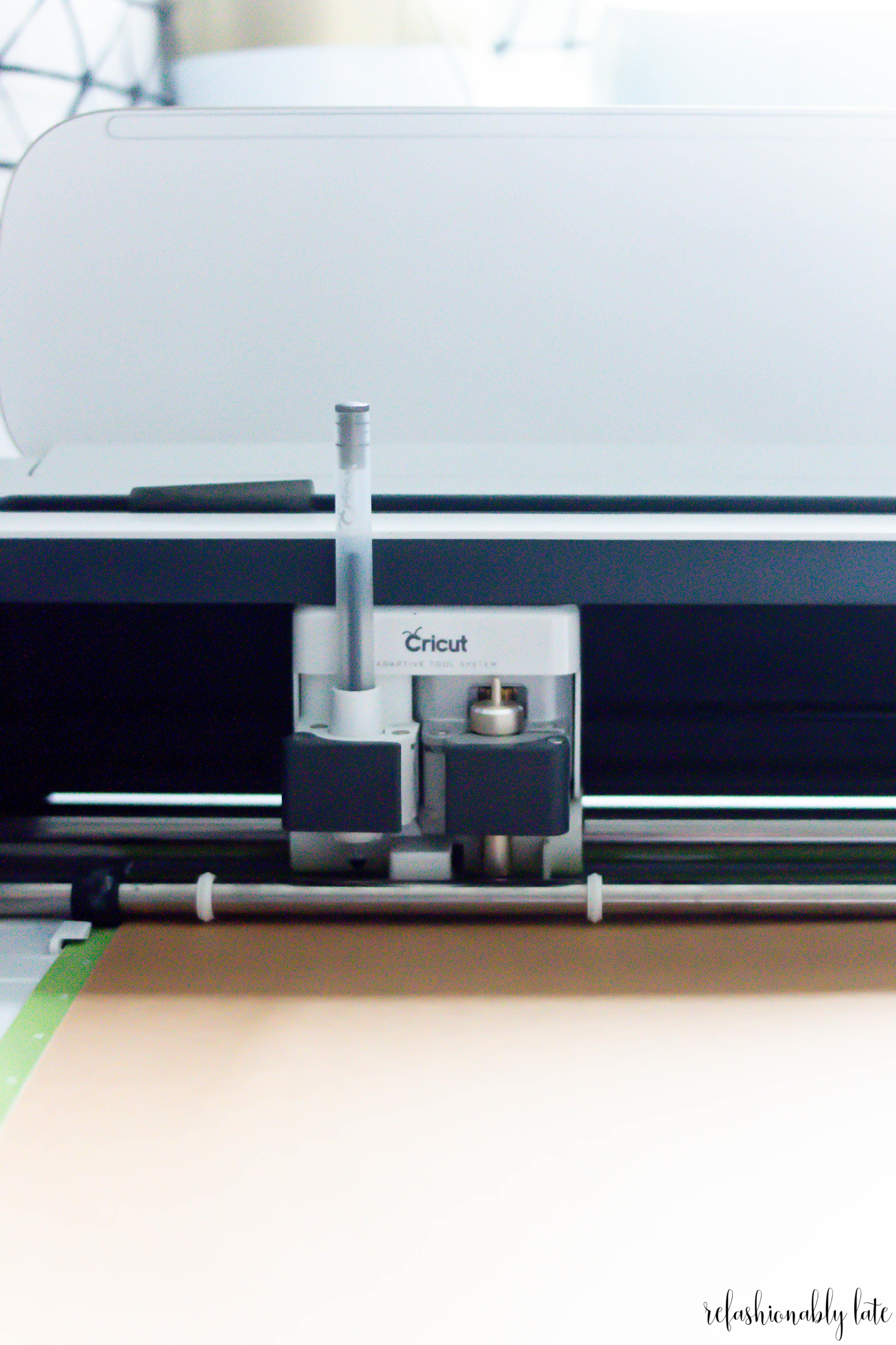 Cricut Maker cutting brown paper with the black glitter gel pen in use