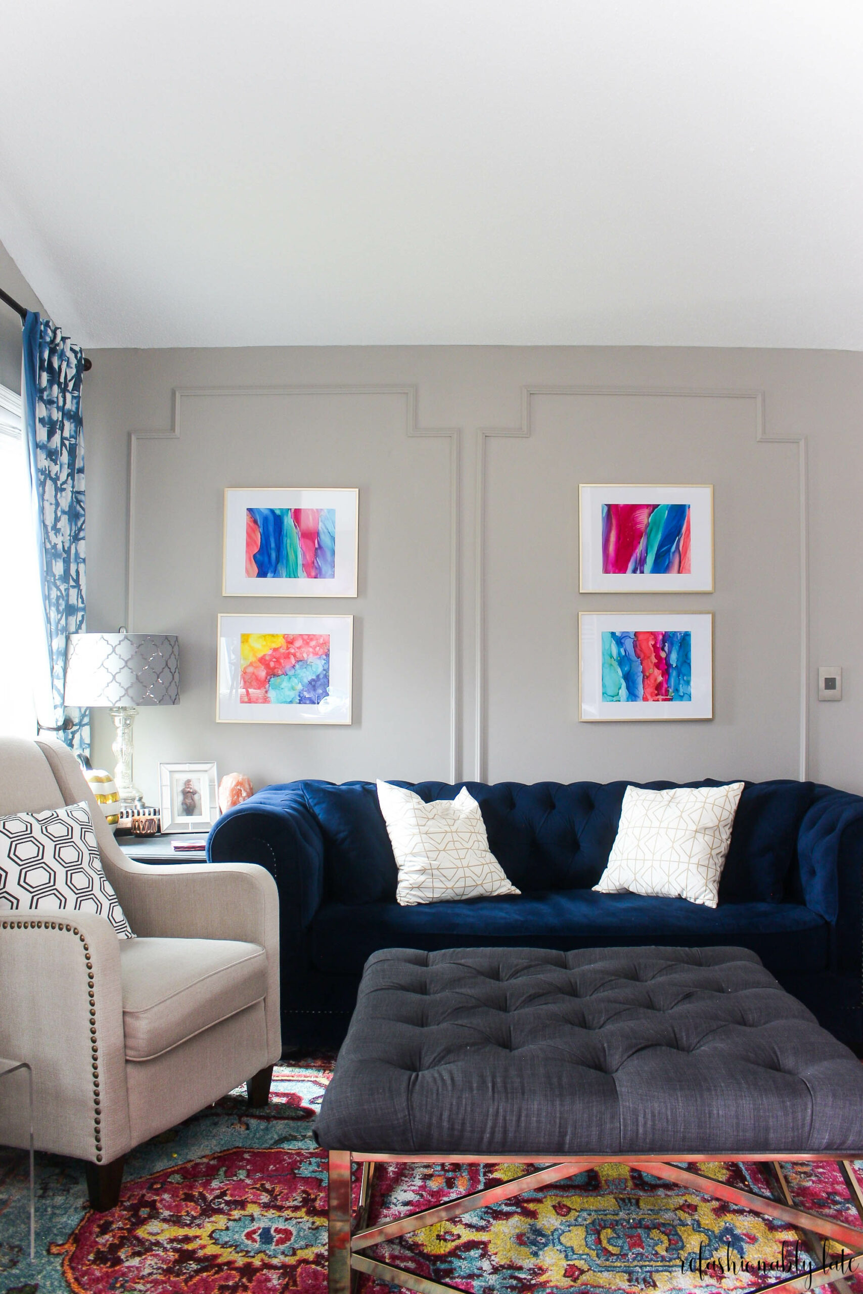 living room with tufted ottoman and bright colored artwork and navy couch