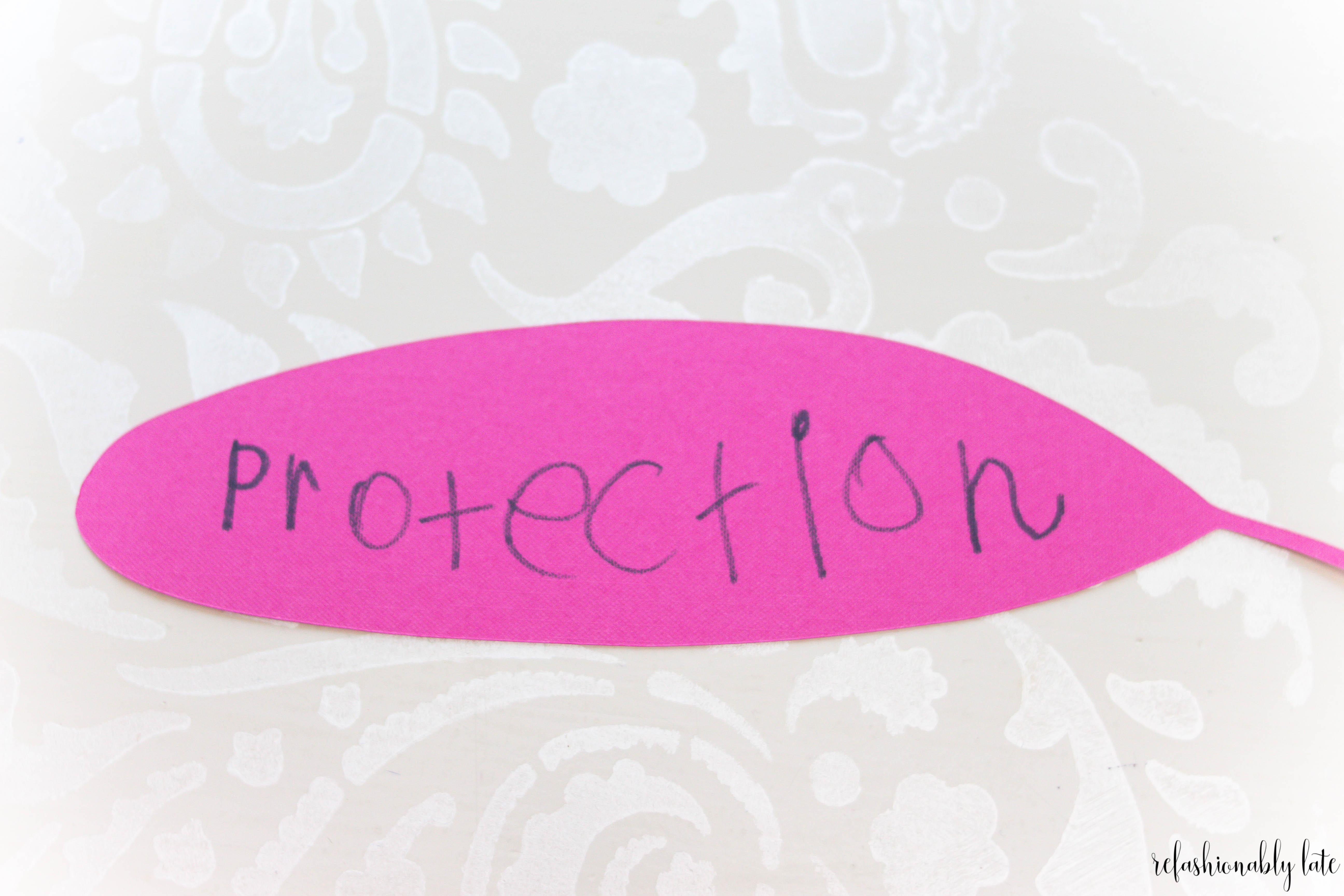 paisley background with pink paper feather with the word protection