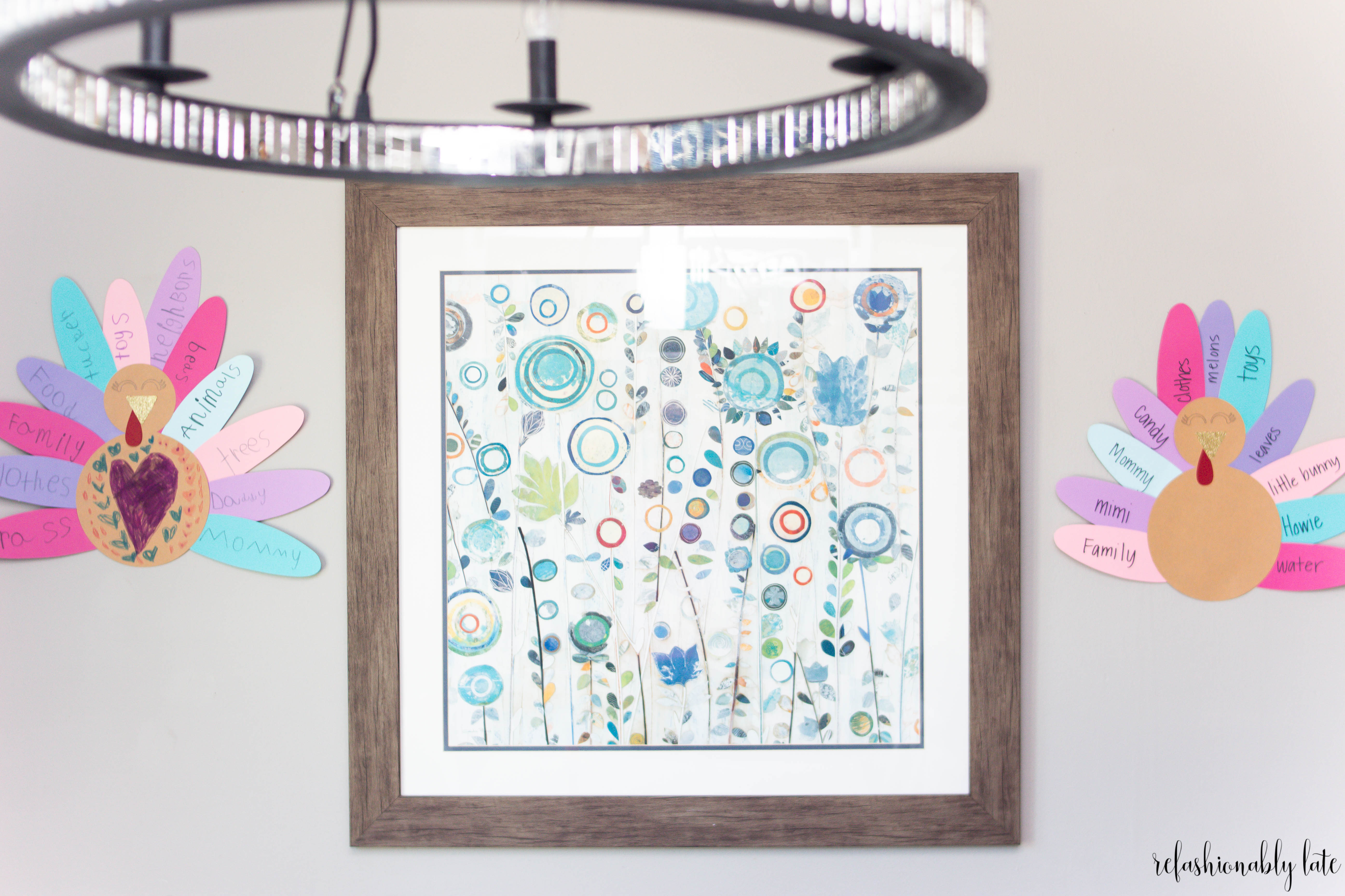 floral photo hung on a gray wall with two paper turkeys on either side