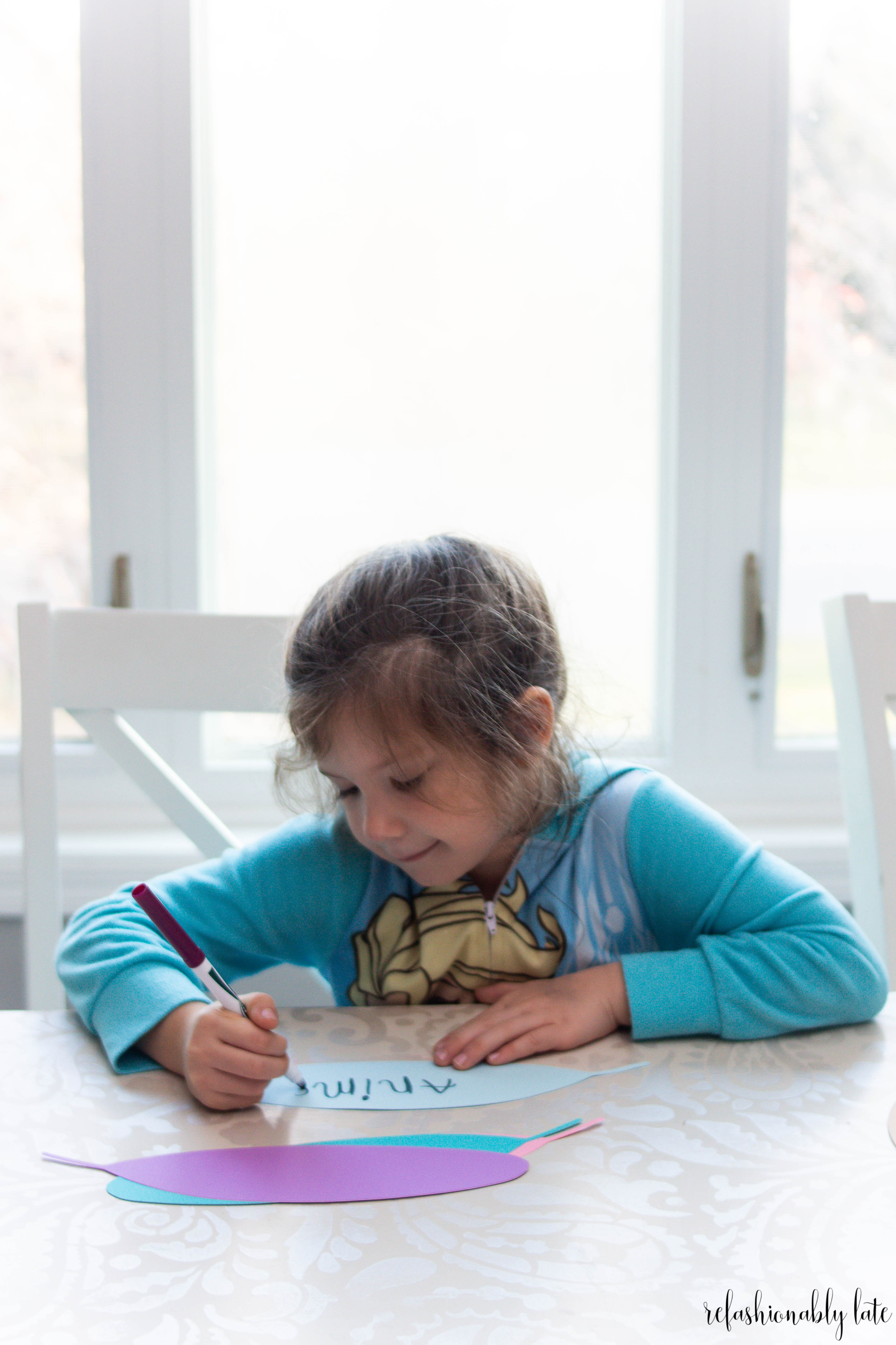little girl writing on paper feathers